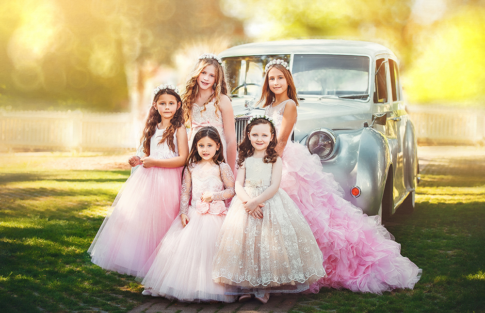 Toronto Fashion photographer catches flower girls on camera posing in front of the vintage car.